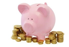 Pink piggy bank surrounded by stacks of gold coins.